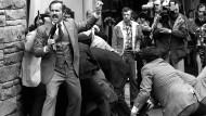 30.März 1981: John Hinckley, der Präsident Reagan und drei seiner Begleiter mit Schüssen verletzt hat, wird von Sicherheitskräften überwältigt und zu Boden gedrückt.
