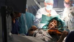 Patientin spielt Geige während ihrer Hirn-OP