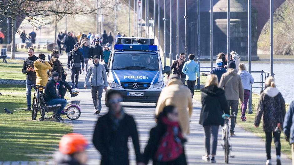 Am Frankfurter Mainufer kontrolliert die Polizei, ob die Spaziergänger die Maßnahmen einhalten.