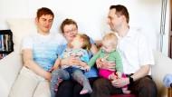 Familienfoto auf dem Sofa zuhause. Die Regenbogenfamilie die Papas Michael und Aron, Mama Franka und ihre beiden Kinder in ihrer Wohnung in Berlin