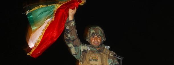 Für Jubelgesten ist es zu früh: Ein Peschmerga-Kämpfer mit der kurdischen Flagge auf dem Weg ins syrische Kobane (Ende Oktober)