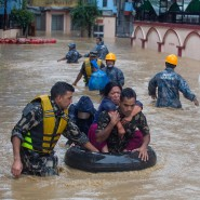 Mitglieder der nepalesischen Armee retten Anwohner mit einem Schwimmring auf einer überfluteten Straße.