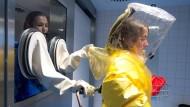 Die Assistenzärztin Maria Koch (r.) demonstriert in einem Schutzanzug die Funktion einer Isolierstation im Robert-Bosch-Krankenhaus in Stuttgart.