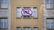 Ein Plakat gegen den Verkauf von Mietwohnungen an die Deutsche Wohnen SE hängt an einer Gebäudefassade in der Karl-Marx-Allee in Berlin.