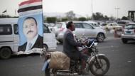Auf dem Motorrad in Sanaa: Vorbei an einer Flagge mit dem Bild des früheren Präsidenten Ali Abdullah Salih.