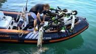 Ein Mann lädt einen Elektro-Roller auf ein Schlauchboot, während freiwillige Taucher an der Küste von Marseille aus dem Meerwasser bergen.