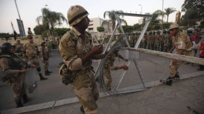 Soldiers pull barbed wire fencing near army soldiers taking positions in front of protesters who are against Egyptian President Mursi, near the Republican Guard headquarters in Cairo