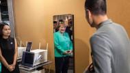 """Wunder der Technik: Merkel steht am Freitag vor einem Spiegel des Unternehmens """"iCarbonX"""", der Gesundheitsdaten anzeigen kann."""