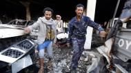 Männer tragen die Leiche eines der Opfer der Luftangriffe aus dem attackierten Gebäude.