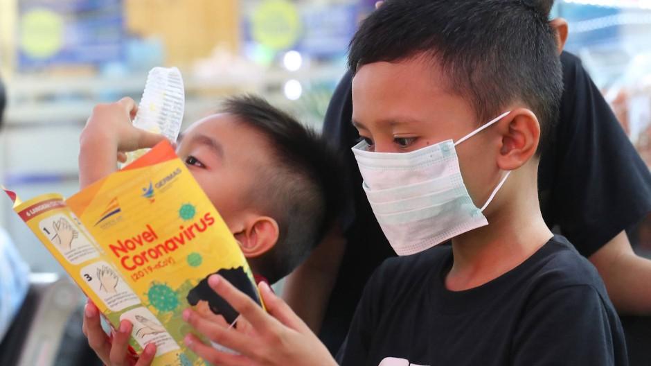 Ein Junge liest ein Informationsblatt über das Coronavirus in Jakarta, Indonesien.