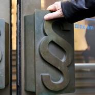 Paragrafen-Symbole sind an Türgriffen am Eingang zum Landgericht in Bonn angebracht.