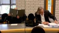 Der Angeklagte schützt sich mit einem Aktenordner vor Gericht.
