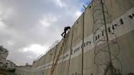 Ein palästinensischer Jugendlicher klettert über die israelische Sperranlage in Ramallah.