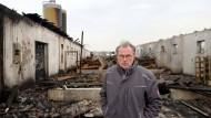 Vor der Ruine: Einer der beiden Ställe von Karl Wilhelm Kliem ist bis auf die Grundmauern abgebrannt, 5000 Hennen verendeten in den Flammen.
