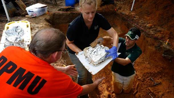Jason Byrd helps University of South Florida assistant professor Erin Kimmerle and assistant professor Christian Wells remove remains from the cemetery at the now closed Arthur G. Dozier School for Boys in Marianna