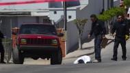 Trauriger Alltag: Ermittler untersuchen einen Tatort in Tijuana, an dem ein Polizist erschossen wurde.