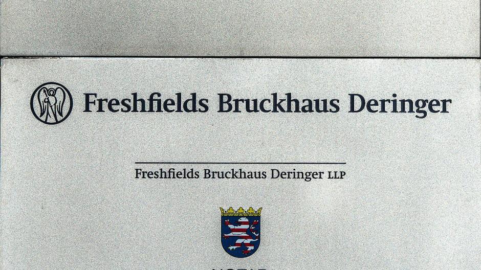 An einem Bürogebäude ist das Firmenschild der Kanzlei Freshfields angebracht.