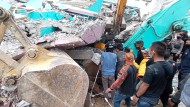 Rettungskräfte suchen in der Stadt Mamuju nach Überlebenden in den Trümmern.