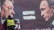 Kiew: Ein Wahlplakat, das den vorherigen ukrainischen Präsidenten Poroshenko und den russischen Präsidenten Putin zeigt, wird nach der Wahl entfernt.