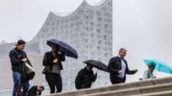 Spaziergänger mit Regenschirmen gehen bei bedecktem Himmel und Nieselregen in Hamburg an der Elbphilharmonie vorbei.