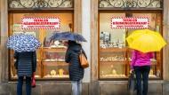 Mehrere Frauen stehen mit Regenschirmen vor einem Schmuckgeschäft, das wegen Geschäftsaufgabe einen Räumungsverkauf durchführt.