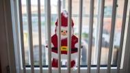 Ein gebastelter Weihnachtsmann klebt in der Frankfurter Justizvollzugsanstalt Preungesheim hinter den Gittern an einer Fensterscheibe.