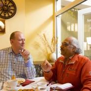 """Subramaniya Suresh (r.) und Steffen Köhler debattieren in einem Restaurant in Ludwigsburg über Fragen wie West-Ost-Gefälle, Einwanderung und bezahlbaren Wohnraum. Das Gesprächspaar hat sich über die Aktion """"Deuschland spricht"""" gefunden."""