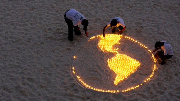 WWF activists light candles representing the earth as they demonstrate on the sidelines of the UN Climate Change Conference COP16 in Cancun