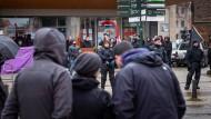 Im Nieselregen Brandenburgs: Im Hintergrund demonstrieren Rechtsextreme, dazwischen Bereitschaftspolizisten, im Vordergrund diskutieren Staatsschutzbeamte.