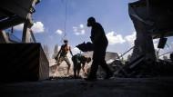 Männer in Donezk räumen nach einem Luftangriff der ukrainischen Armee Schutt beiseite