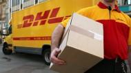Gleich klingelt es: Ein Postbote liefert ein Paket aus.