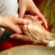 Eine Schwester hält einer sterbenden Frau die Hand (Symbolbild)