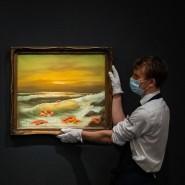 """Ein Galerie-Assistent hält ein Gemälde des Triptychons """"Mediterranean Sea View 2017""""."""