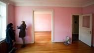 Interessenten messen bei einer Wohnungsbesichtigung eine Mietwohnung aus