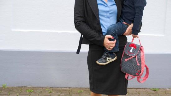 Eine berufstätige Mutter bringt ihr Kind in die Kita.