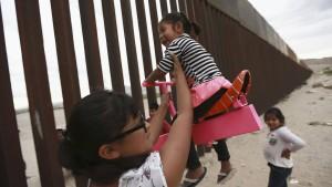 Mexikaner und Amerikaner durchbrechen Grenzzaun mit Wippen