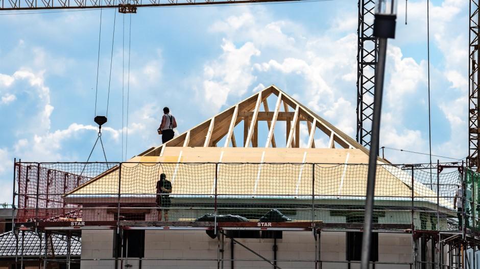 Dachdecker errichten mit Holz den Dachstuhl für ein Haus in einem hessischen Neubaugebiet.