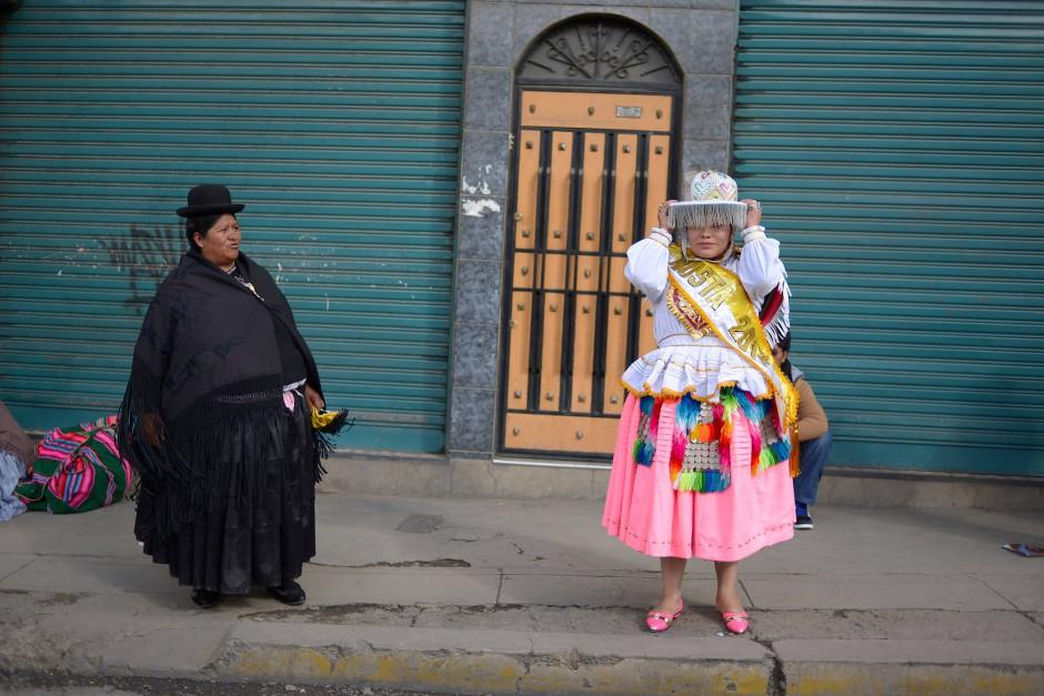 Eine traditionell gekleidete Cholita beobachtet ihre Tochter, während sie sich ihren Hut zurechtrückt, um bei einem Preste-Fest in La Paz teilzunehmen.