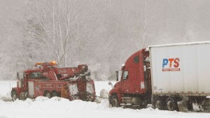Large tow truck pulls freight truck out of snow in Garrett County western Maryland