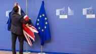 Ein EU-Mitarbeiter hängt vor den Brexit-Verhandlungen in Brüssel die britische Fahne auf.