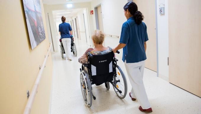 Zwei Pflegerinnen schieben im Asklepios-Klinikum Wandsbek Patienten mit Rollstühlen durch einen Flur.