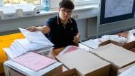 Kampf mit der Wahl: Ein Mitarbeiter der Stadtverwaltung in Bad Homburg stellt Unterlagen für die Briefwahl zusammen.