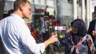 Berliner BEgegnungen: Michael Müller überreicht eine Rose.