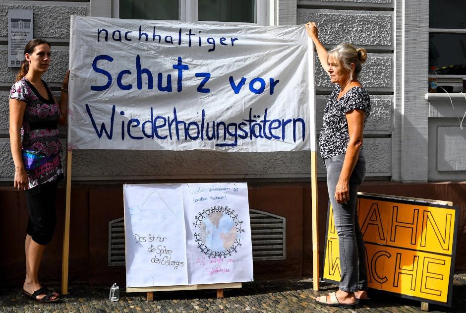"""Mitglieder der Initiative """"Aktiv gegen Missbrauch"""" halten mit Bannern vor dem Landgericht eine Mahnwache."""