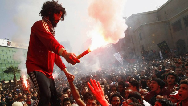 "Al Ahly fans, known as ""Ultras"", celebrate and shout slogans in front of the Al Ahly club after hearing the final verdict of the 2012 Port Said massacre in Cairo"
