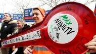Mit einem Signalflügel, Plakaten und Trompeten unterstützen Eisenbahnerinnen und Eisenbahner der Eisenbahn- und Verkehrsgewerkschaft (EVG) die Verhandlungsdelegation zu Beginn der Gespräche zwischen EVG und der Deutschen Bahn am Verhandlungsort.