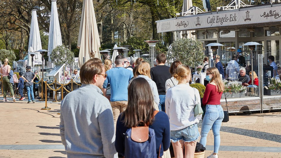 Menschen stehen am Sonntag in Timmendorfer Strand vor einem Cafe an.