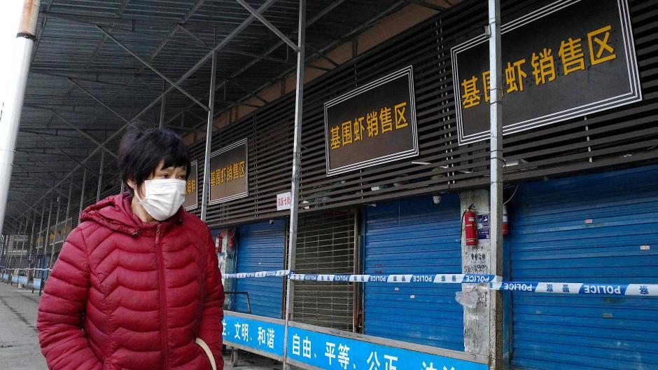 Eine Frau überquert den Fischmarkt in Huanan, der als Ausbruchsort des neuartigen Virus gilt. Er wurde darafhin von den Behörden geschlossen.