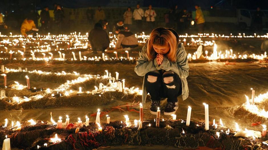 Trauernde gedenken in einem Park im japanischen Kobe der Toten des Erdbebens vor 25 Jahren.
