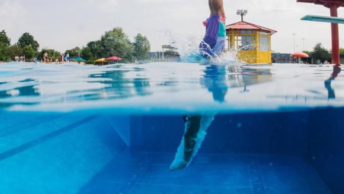 Ein Schwimmer springt in Düsseldorf vom Sprungturm ins Wasser.